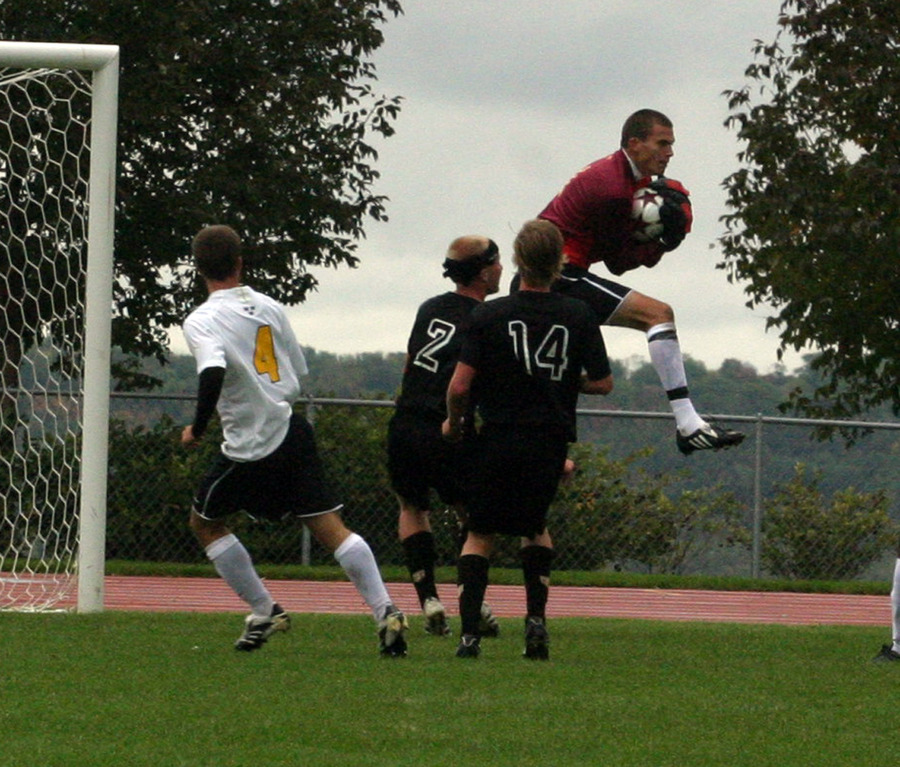 Gustavus goalkeeper Luke Strom goes up to make a save.