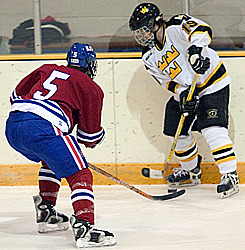 Gustie forward #19 Andy Hogan gets ready to clear the puck as Johnnie defensman Sam Dorr closed down on him.