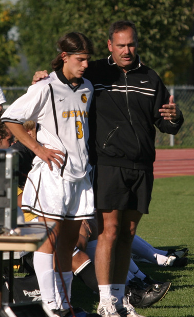 Coach Zelenz chats with junior midfielder Chris Pinahs before he re-enters the match.